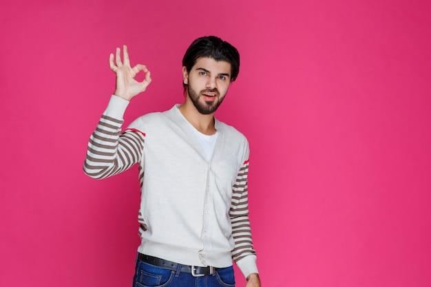 Człowiek w białej koszuli czyniąc znak ręką pełnej satysfakcji lub medytacji.