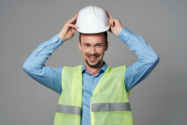 Człowiek w białym hełmie plany budowniczy jasne tło