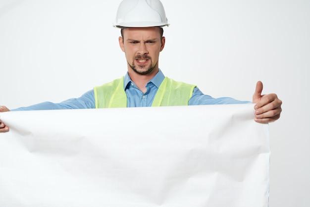 Człowiek w białym hełmie plany konstruktora pracy zawodowej