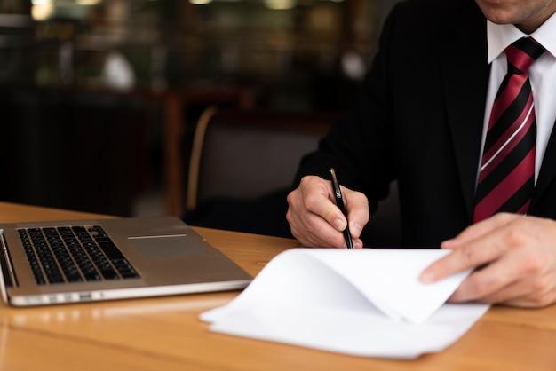 Człowiek w biurze pisania na papierze