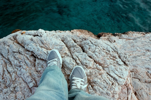 Człowiek w butach trekkingowych stoi na skraju urwiska. podróż koncepcyjna, spacery nad morzem, myśli samobójcze, depresja.