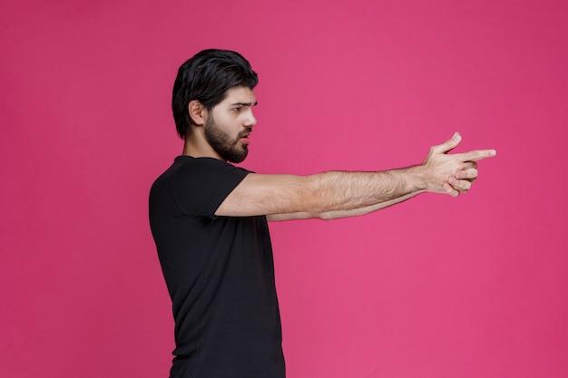 Człowiek w czarnej koszuli co znak pistoletu