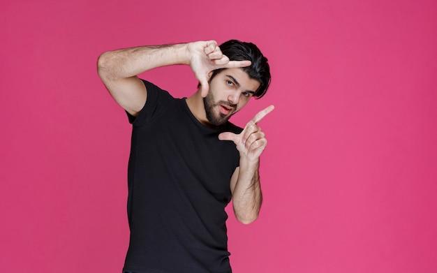 Człowiek w czerni oddając ręce jak ramka na zdjęcia
