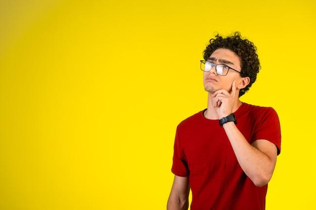 Człowiek w czerwonej koszuli myśli i planowania.