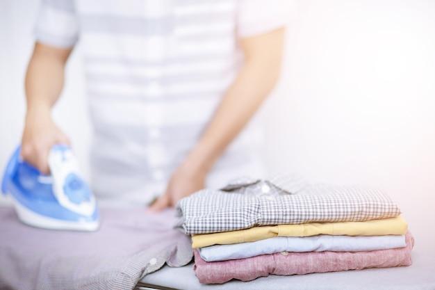 Człowiek w domu prasowanie elektryczne i stos różnych kolorów ubrań.