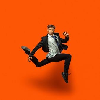 Człowiek w dorywczo biuro styl ubrania skoki i taniec na białym tle na jasnym pomarańczowym tle. koncepcja biznesowa, start-up, open-space, inspiracja. elastyczny taniec baletowy. spieszę się, piję kawę.