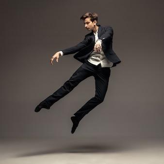 Człowiek w dorywczo biuro styl ubrania skoki i taniec na białym tle na szarym tle. sztuka, ruch, akcja, elastyczność, koncepcja inspiracji. elastyczna kaukaska tancerka baletowa, skoki w stanie nieważkości.