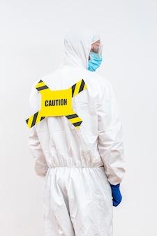 Człowiek w garnitur hazmat ze znakiem niebezpieczeństwa