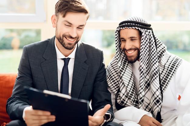 Człowiek w garniturze wyjaśnia arabskiemu inwestorowi, jak będą działać pieniądze