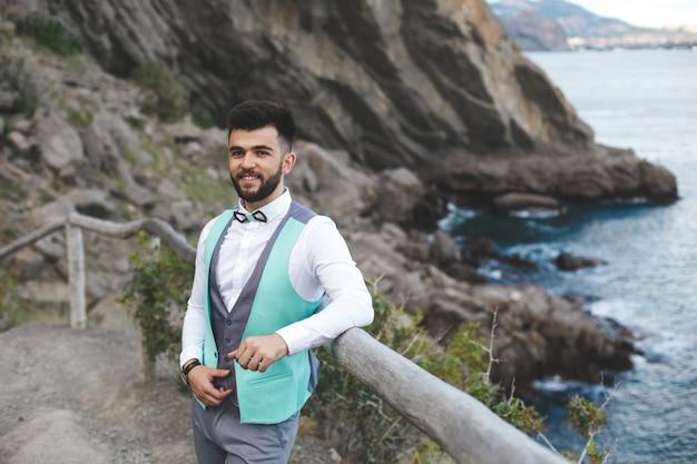Człowiek w garniturze z natury. portret pana młodego. uśmiecha się