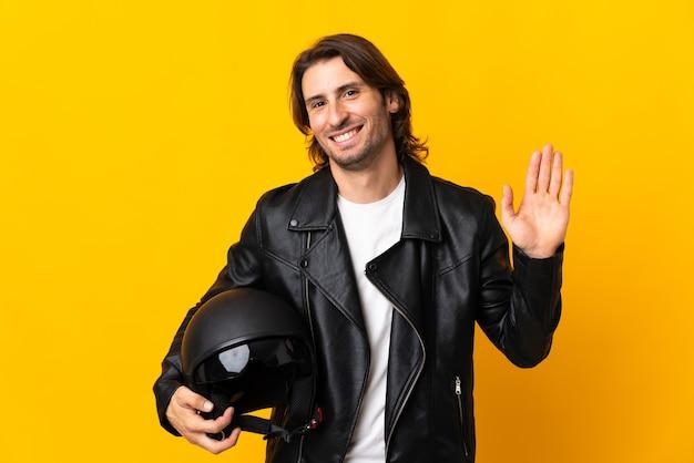 Człowiek w kasku motocyklowym na białym tle na żółtej ścianie, salutując ręką z happy wypowiedzi