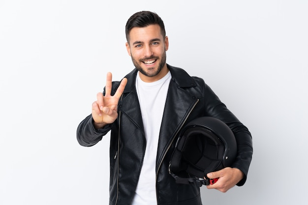 Człowiek w kasku motocyklowym uśmiecha się znak zwycięstwa i pokazuje