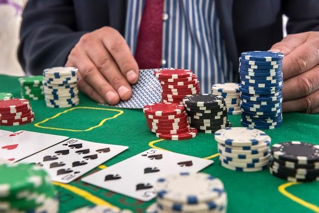 Człowiek w kasynie patrząc na karty do gry i stos żetonów