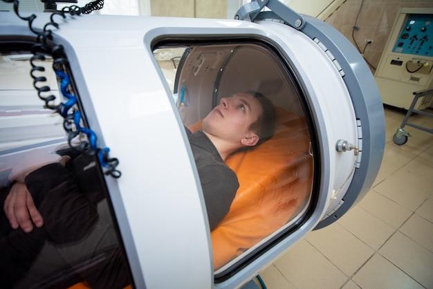 Człowiek w komorze hiperbarycznej, leczenie tlenem, komora medyczna