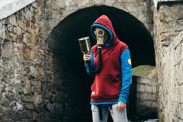 Człowiek w masce gazowej w starym kamiennym tunelu
