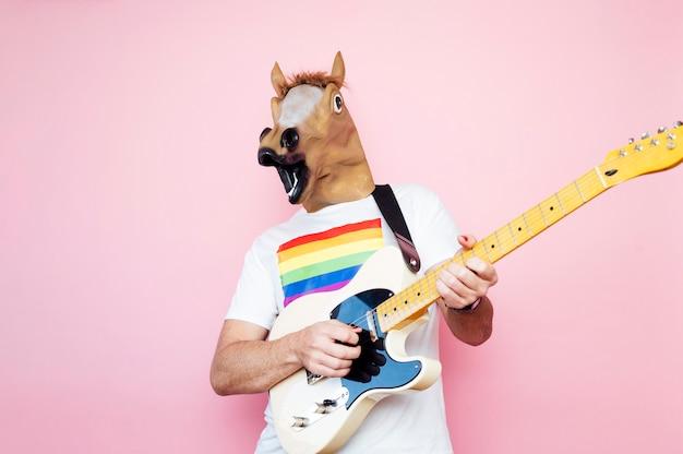 Człowiek w masce konia grający na gitarze elektrycznej.