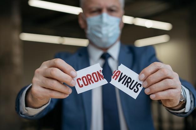 Człowiek w masce ochronnej rozdzierającej papier ze słowem koronawirus