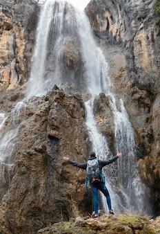 Człowiek w naturze przy wodospadzie