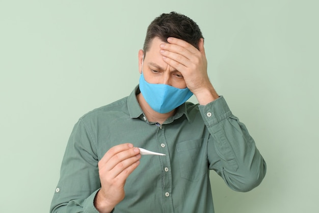 Człowiek w ochronnej masce medycznej iz termometrem na kolorowym tle