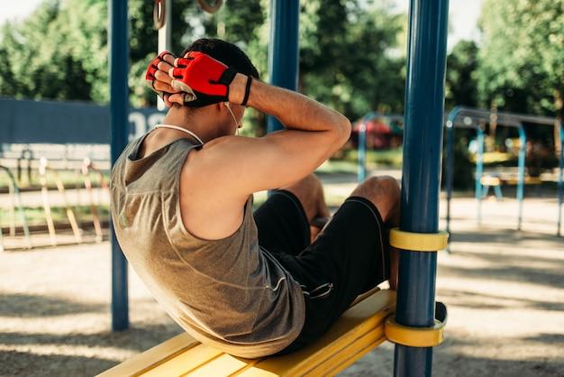 Człowiek w odzieży sportowej robi ćwiczenia na prasie, widok z tyłu, trening fitness na świeżym powietrzu. silny sportowiec na treningu sportowym w parku