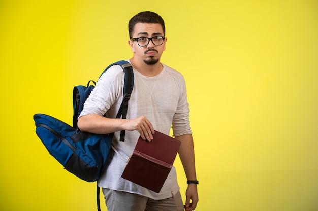 Człowiek w okularach trzymając książkę.