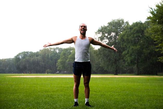 Człowiek w parku z szeroko otwartymi ramionami