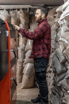 Człowiek w pomieszczeniu z kotłem na paliwo stałe, pracujący na biopaliwo, oszczędne ogrzewanie.