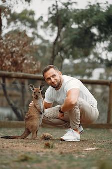 Człowiek w rezerwie bawi się kangurem