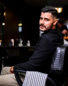 Człowiek w salonie fryzjerskim patrząc w bok