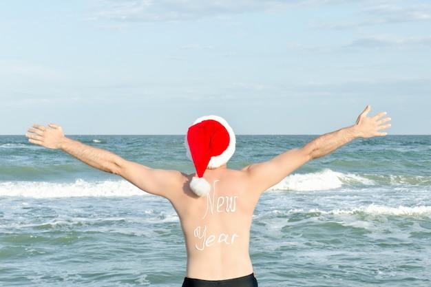 Człowiek w santa hats z napisem nowy rok z tyłu nad brzegiem morza. ręce do góry. widok z tyłu
