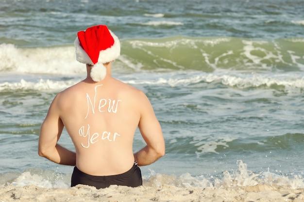 Człowiek w santa kapelusze z napisem nowy rok na plecach na plaży. widok z tyłu