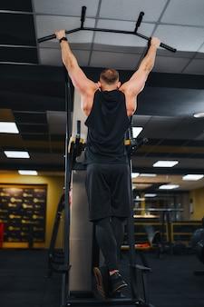 Człowiek w siłowni, ćwiczenia na poprzeczce w siłowni