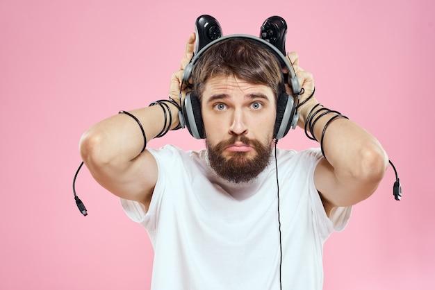 Człowiek w słuchawkach z joystickami w rękach, grając w gry