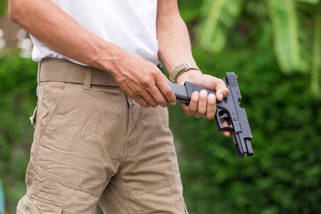Człowiek w spodnie cargo z pistoletem
