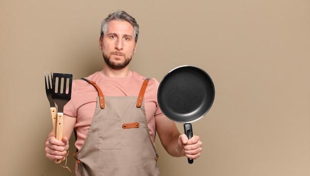 Człowiek w średnim wieku kucharz. koncepcja grilla