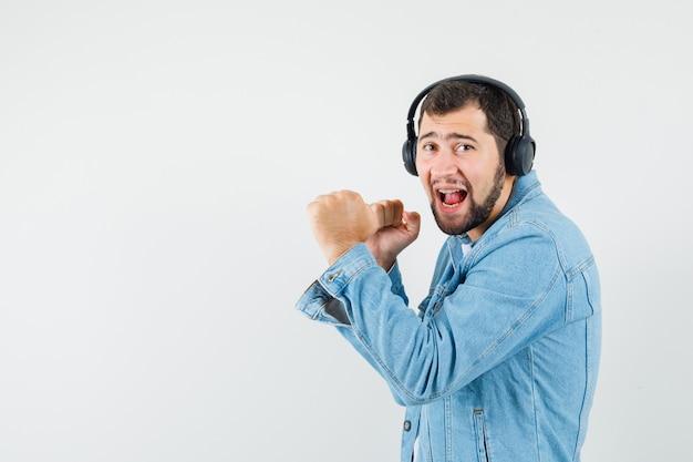 Człowiek w stylu retro słuchanie muzyki ze słuchawkami w kurtce, t-shirt i patrząc rozbawiony, widok z przodu. miejsce na tekst