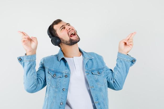 Człowiek w stylu retro słuchanie muzyki ze słuchawkami w kurtce, t-shirt i patrząc rozbawiony, widok z przodu.