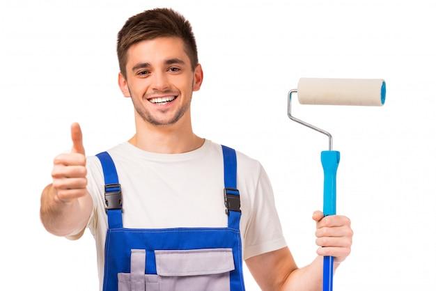 Człowiek w ubraniach roboczych maluje ściany w pokoju.