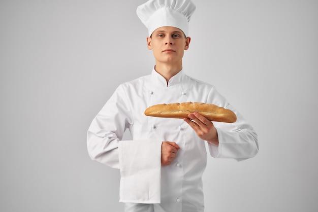 Człowiek w ubraniach szefów kuchni profesjonalnej pracy piekarni jasnym tle