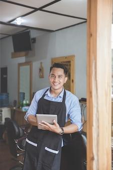 Człowiek w zakładzie fryzjerskim z cyfrowego tabletu