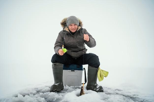 Człowiek w zimowe ubrania, wędkowanie samotnie na zewnątrz