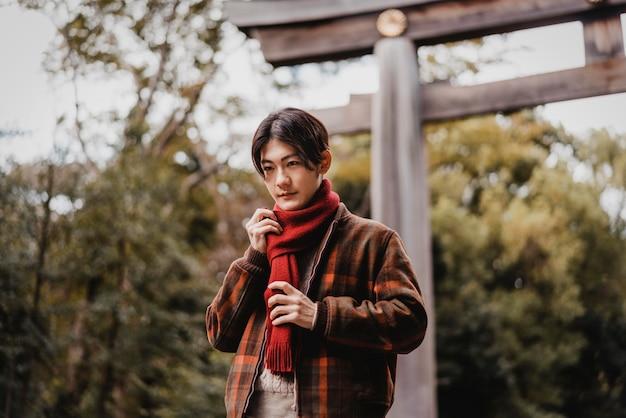 Człowiek w zimowy strój pozowanie na zewnątrz przed bramą