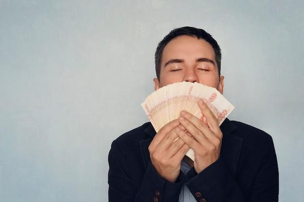 Człowiek wąchający dolary. słodki zapach pieniędzy. młody chłopak wącha 5000 rubli zarobione pieniądze. pensja. łatwe pieniądze. pakiet pieniędzy