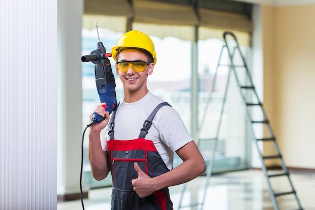 Człowiek, wiercenie ściany za pomocą perforatora wiertarki
