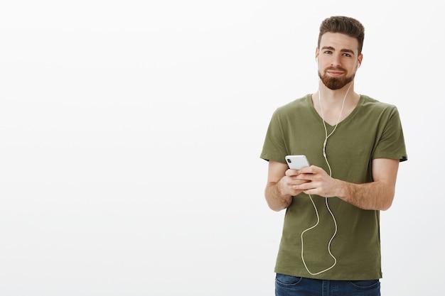 Człowiek włożony w piosenkę przynosi miłe wspomnienia. portret czarującego, słodkiego i delikatnego brodatego chłopaka w oliwkowej koszulce, uśmiechnięty zachwycony zrelaksowanym uśmiechem, gdy słucha muzyki w słuchawkach, trzymając smartfon