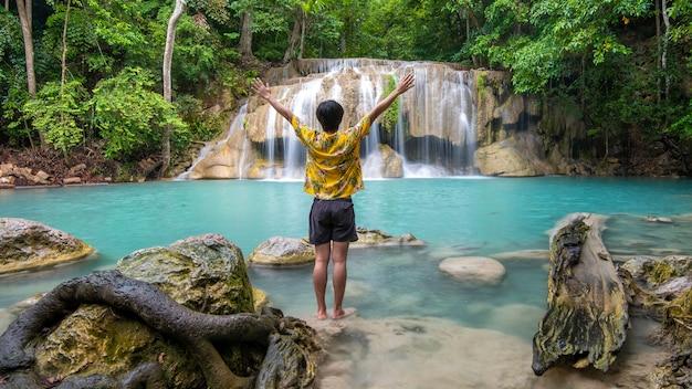 Człowiek wolności cieszy się z pięknym wodospadem w tropikalnym lesie