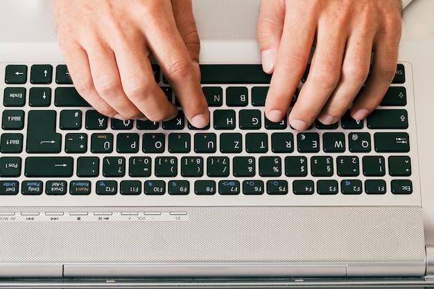 Człowiek, wpisując na klawiaturze komputera