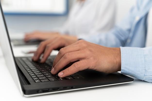 Człowiek wpisując na klawiaturze laptopa