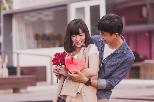 Człowiek wręczając prezent i róż do kobiety