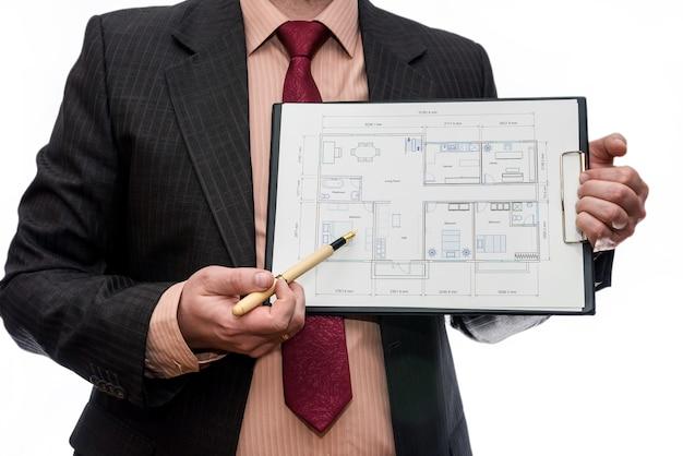 Człowiek, wskazując na plan domu na białym tle na białej ścianie